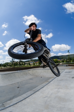 BMX rider jumps while doing cross bar trick. photo