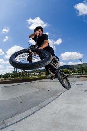 BMX rider jumps while doing cross bar trick.