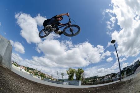 Bmx rider on a big air jump in a skate park.