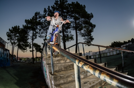Biker doing peg grind down the hand rail over the stairs photo