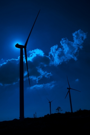 Wind turbine in the back light of the moon with blue sky and clouds. photo