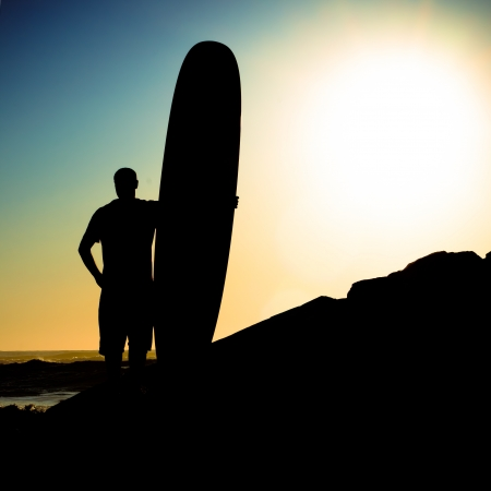 A long boarder watching the waves at sunset in Portugal. photo