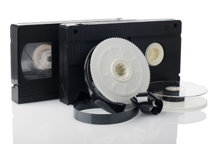 Two videotapes and reel on  white reflective background. photo