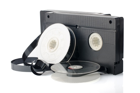 Two videotapes and reel on  white reflective background. Stock Photo