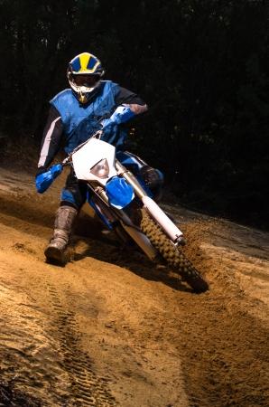 Enduro bike rider on action. Turn on sand terrain. Stock Photo - 16711227