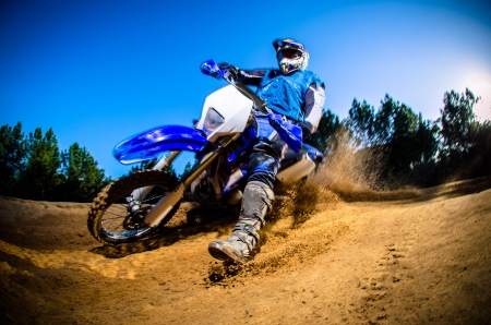 dirt road: Enduro bike rider on action. Turn on sand terrain.