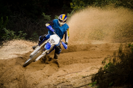 Enduro bike rider on action. Turn on sand terrain. Stock Photo - 16711248