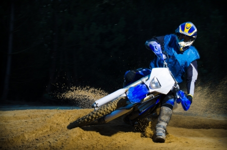 Enduro bike rider on action. Turn on sand terrain. photo