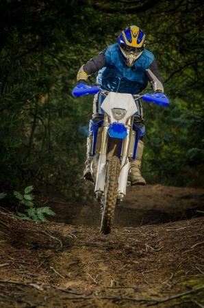 Enduro bike rider on action. Small jamp on muddy terrain. Standard-Bild