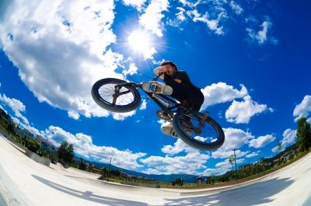 BMX-Fahrer springt, während Sie Querbalken Trick.