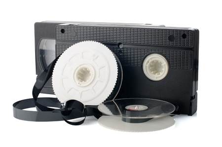 vhs videotape: Two videotapes and reel on  white reflective background. Stock Photo