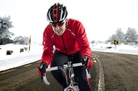 road bike: Cyclist on road bike through a asphalt road in the mountains with snow. Stock Photo