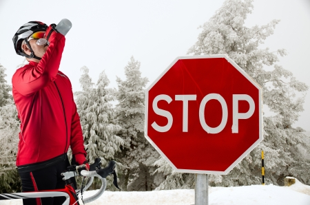 rapidity: Cyclist on road bike near a stop sign in the mountains with snow.