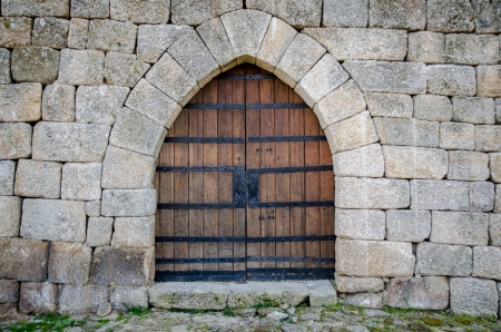 Old medieval castle gate in a fortified granite wall.