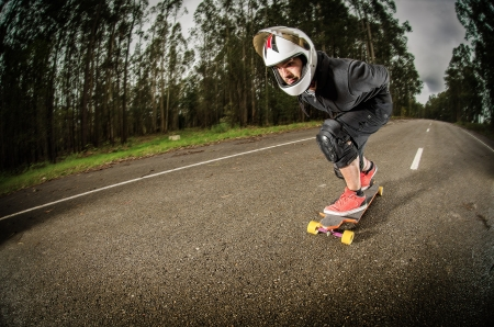 Downhill skateboarder in action on a asphalt road. photo