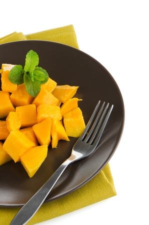 mango fruta: Fruta del mango en la placa de color marr�n sobre fondo blanco.