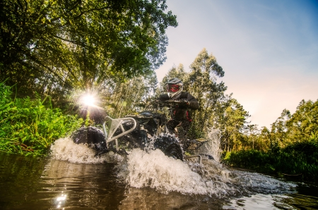 extreme angle: Quad rider through water stream in the forest against sunlight. Stock Photo