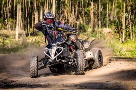 quad: ATV racer takes a turn during a race on a dusty terrain. Stock Photo