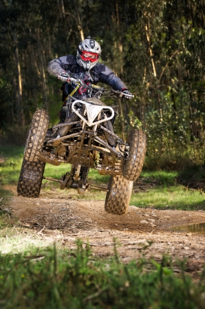 dirt bikes: Quad rider jumping on a forest trail.
