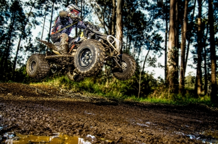 offroad: Quad rider jumping on a muddy forest trail.