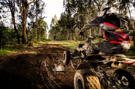 the rider: Quad rider saltare su un sentiero nel bosco fangoso.