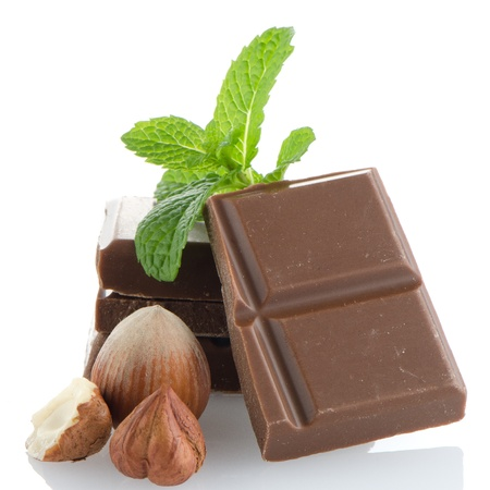 Chocolate Bar with hazelnuts and fresh mint on white background photo