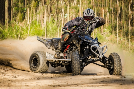 ATV racer takes a turn during a race on a dusty terrain. Banco de Imagens