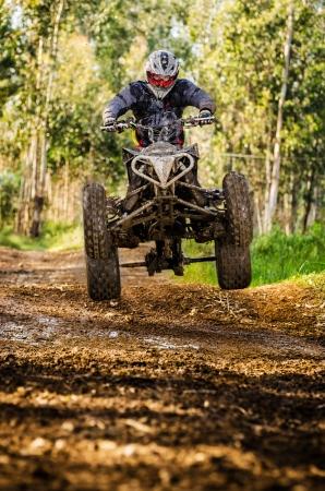 Quad-Fahrer springt auf einem Waldweg.
