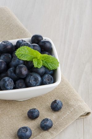 Fresh healthy blueberries in small bowl on wood table photo
