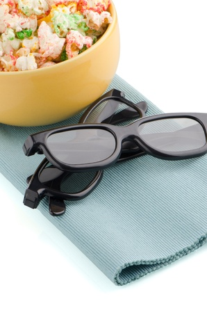 Bowl of popcorn and 3D movie glasses on white reflective background. photo