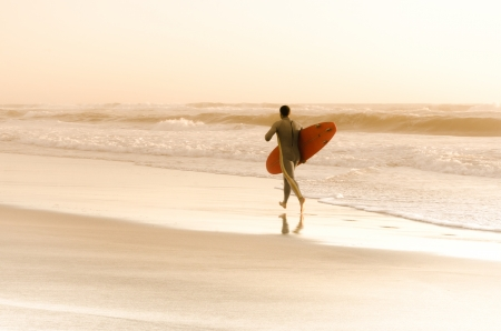 Surfer running on the beach with the waves at sunset in Portugal.