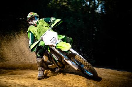 the dirt: Enduro bike rider on action. Turn on sand terrain.