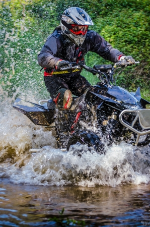 Quad rider through water stream in the forest. photo
