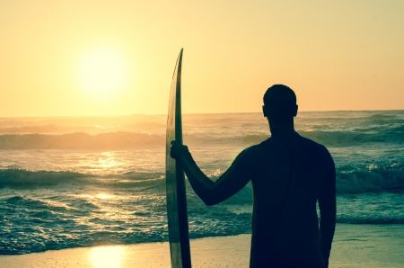 Surfer watching the waves at sunset in Portugal. photo