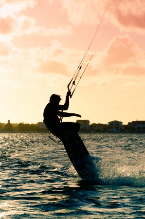 Silhouette of a kitesurfer flying above the water at sunset photo