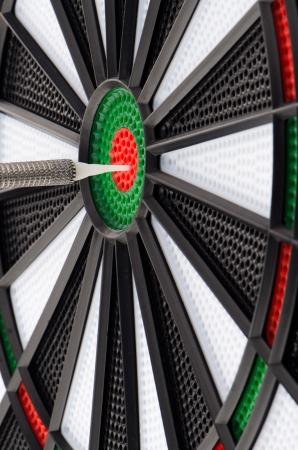 holed: Closeup of dart board with dart.