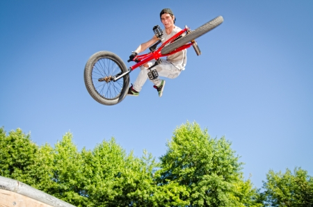 quater: Bmx rider performing a tail whip at a quater pipe ramp on a skatepark.