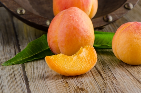 Apricots with leaves on the wooden table.