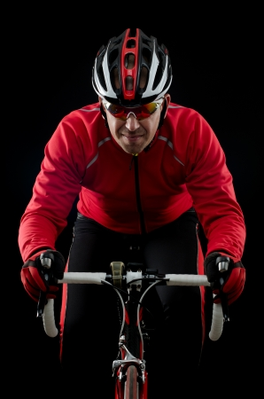 rapidity: Cyclist on road bike on black background.