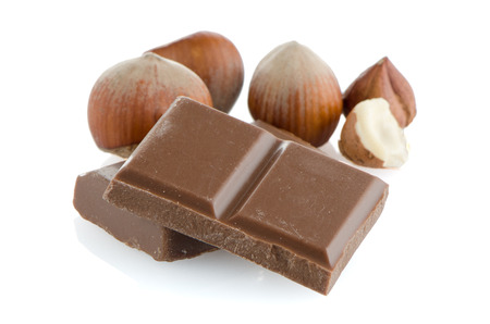 Chocolate parts and hazelnuts isolated on white background.