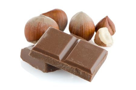 Schokolade Teile und Haselnüsse auf weißem Hintergrund.