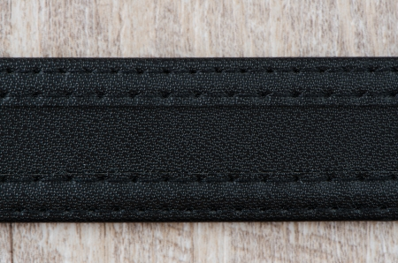 Leather belt over wooden background. photo