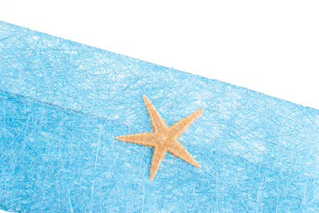 Blue envelope made of blue straw mesh  with sea star decoration on white background. photo