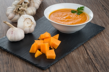 Pumpkin soup on white wood background.