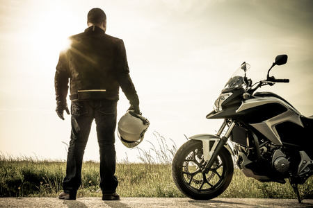 Biker standing with its motorbike on a misty sunset. photo
