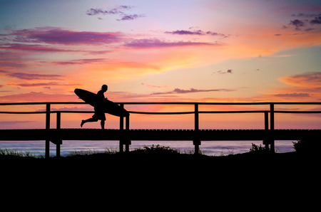 A surfer running to the beach at sunset in Portugal.