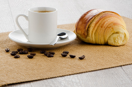 baclground: Cup of black coffee over sackcloth baclground.