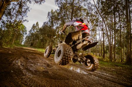 Quad-Fahrer springt auf einem schlammigen Waldweg.