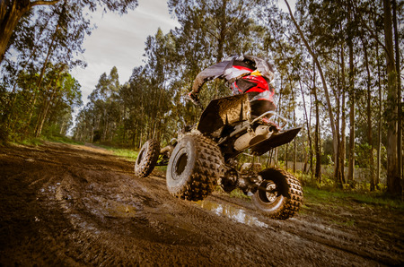 dirt bikes: Quad rider jumping on a muddy forest trail.