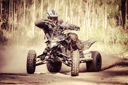 ATV racer takes a turn during a race on a dusty terrain. Stock Photo